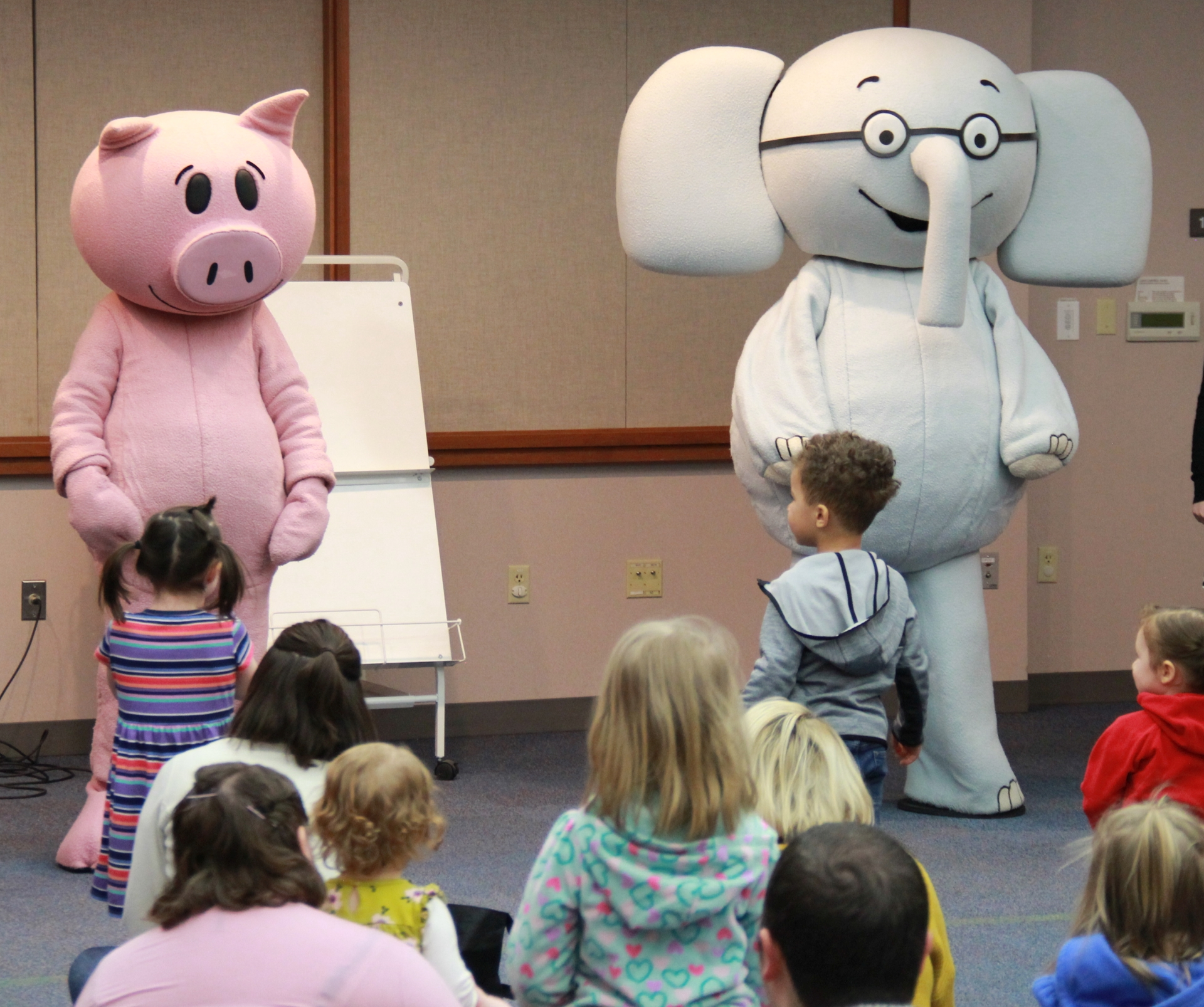 People in pig and elephant mascot costumes performing for a group of intrigued toddlers