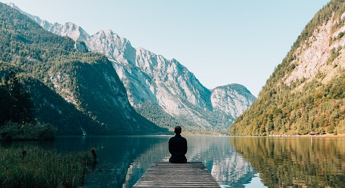 Person sitting on a dock at a lake in the mountains.