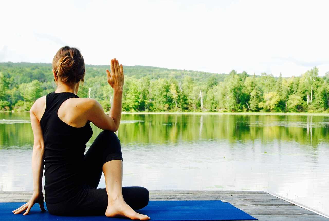 woman doing yoga by a lake
