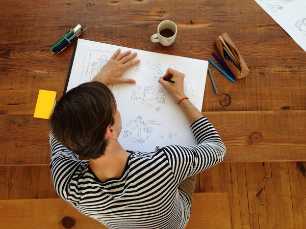 photo of person at a table drawing on paper