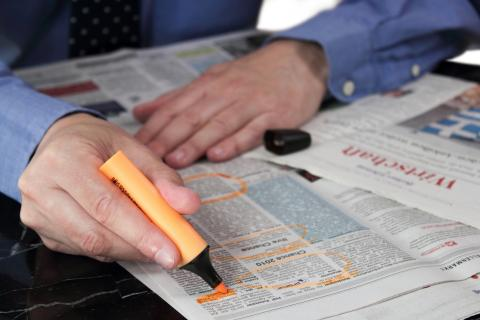 Hands circling job postings in a newspaper