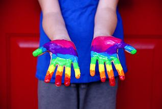 Hands covered in rainbow paint